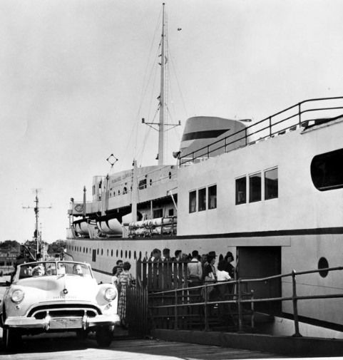 B&W photo pf a white car next to a large white and grey boat.