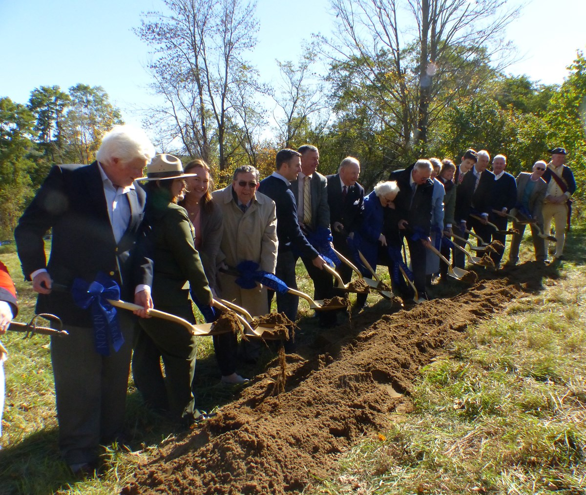 Fifteen people plant shovels in the dirt to break ground for a new monument.