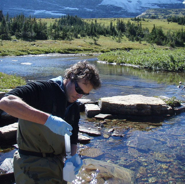technician wearing plastic gloves and adding a water sample to collection bottle, with stream, forest, and mountains in the background