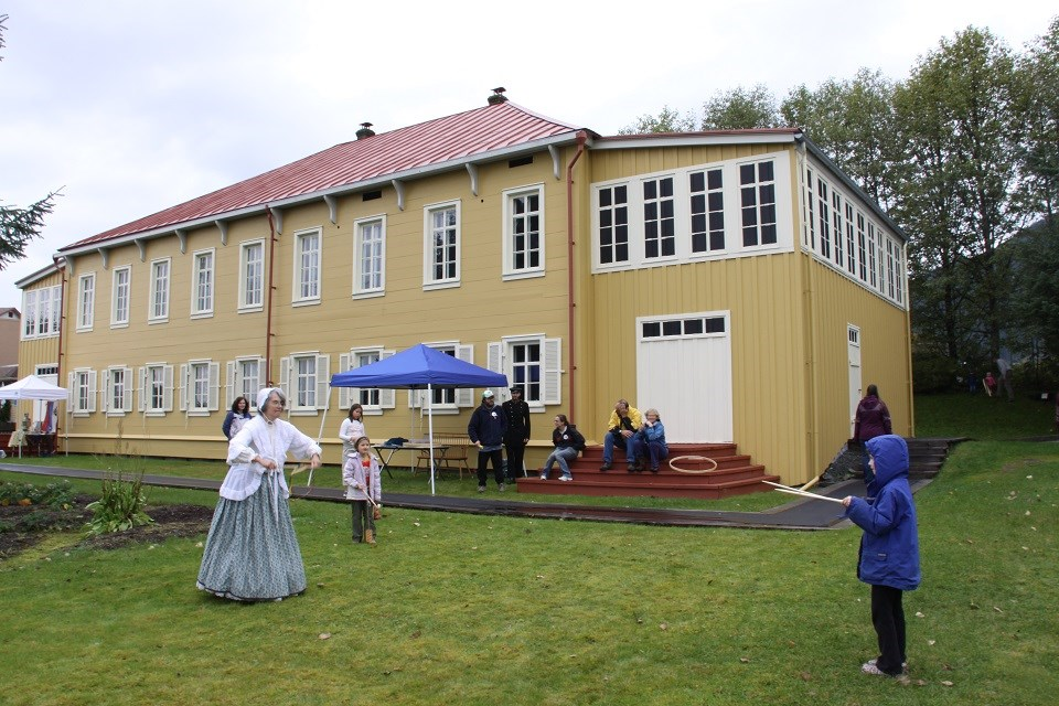 Living historians demonstrating a game to a child in front of a historic yellow house