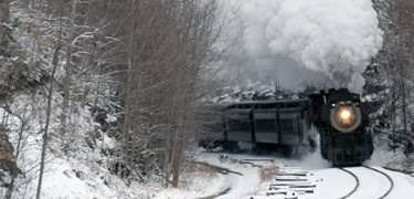 Steam engine moving through a winter landscape