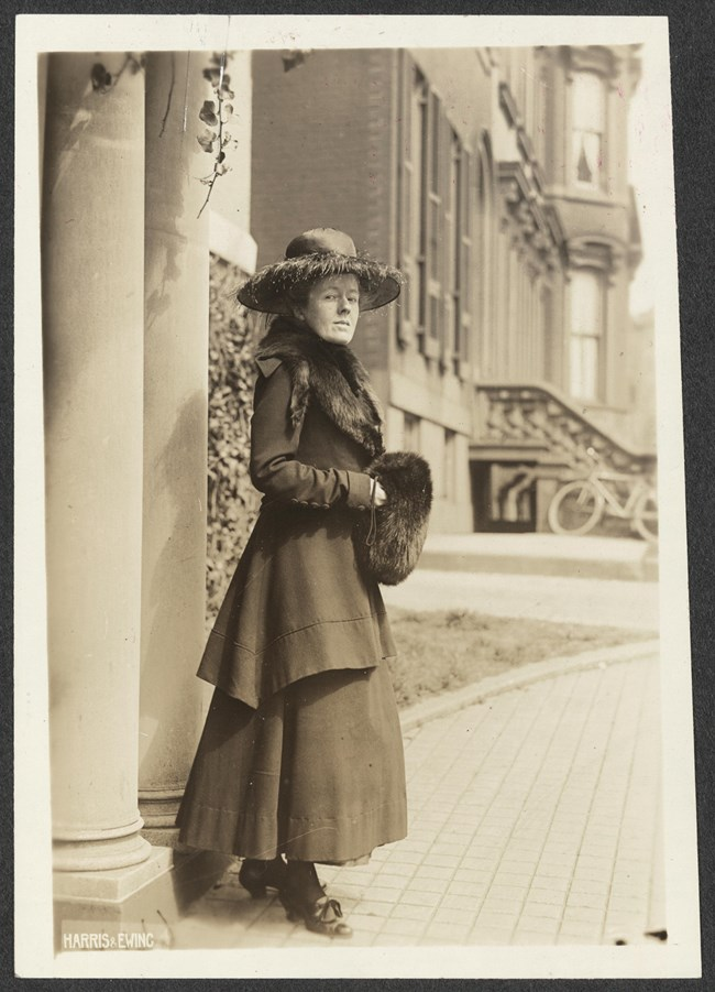 Informal portrait, full-length, Sallie Hovey of New Hampshire, facing right with head turned toward camera, standing outside by column of what is likely National Woman's Party headquarters, wearing two-piece suit with long skirt, fur stole, wide-brimmed h