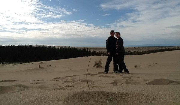 A man and woman stand on sand dunes.