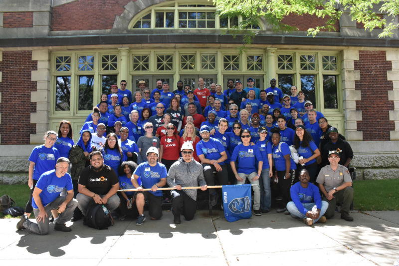 Group photo of 100 plus volunteers from the Mission Continues on the steps of the National Museum of Immigration on Ellis Island