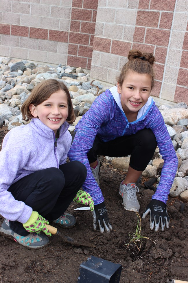 Two young girls smile at the camera as they place a small green plant in the ground