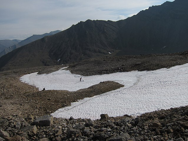 a large patch of snow in a rocky bowl at the top of a mountain