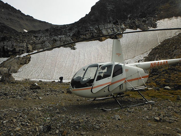 a helicopter parked next to a snow field on a mountainside