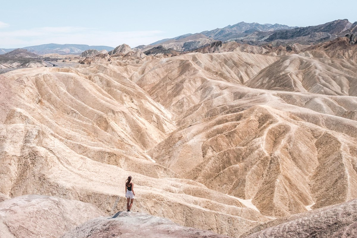 lone woman looks down on badlands with mountains in background