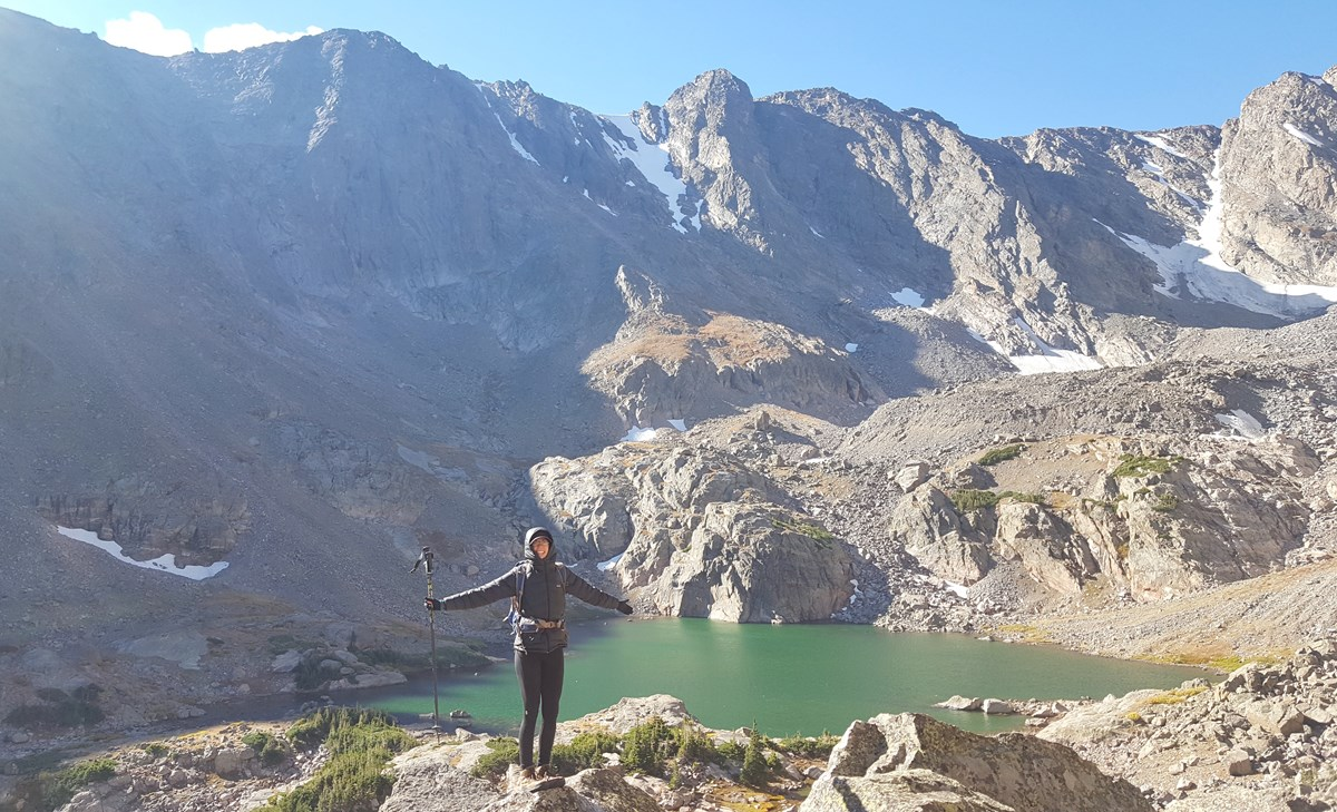 hiker with alpine lake and mountains behind her
