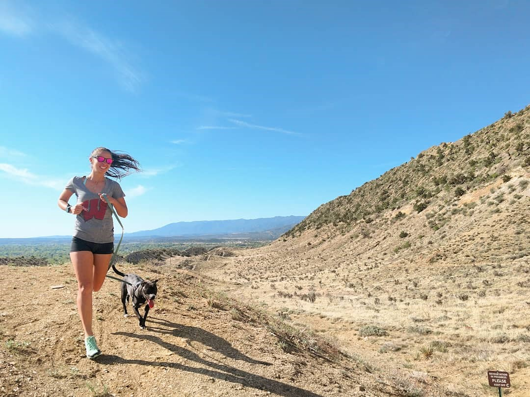 woman and dog run in foothills