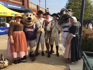 People in period costumes and a costumed bear mascot pose for a photograph.