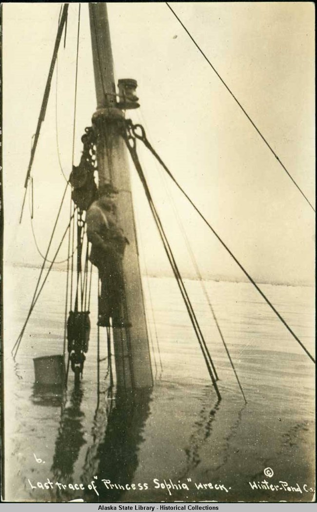 Man standing on foremast of a sunken ship in water.