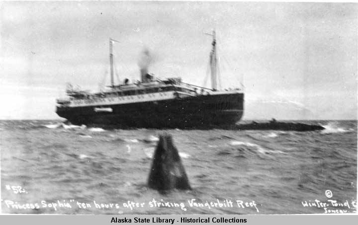 Historical, black and white image of a ship stranded on a reef in choppy ocean water.