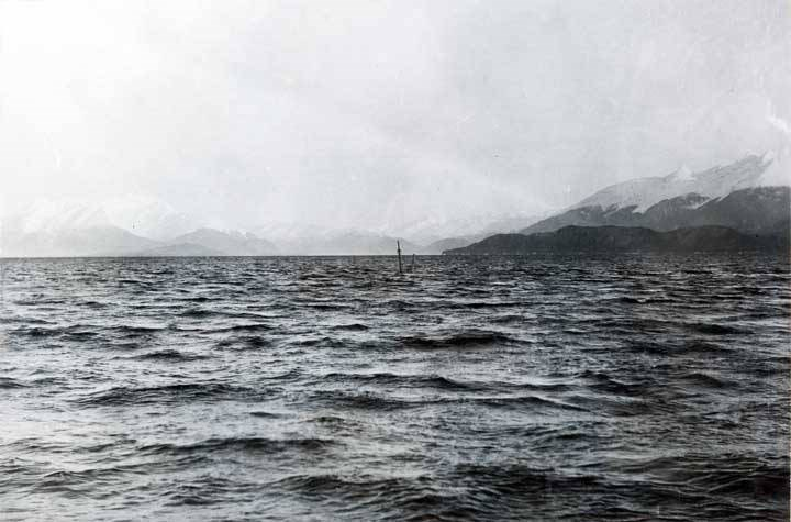 Image of sunken ship with tip of ship mast sticking out of a large body of water. Mountains in the background.