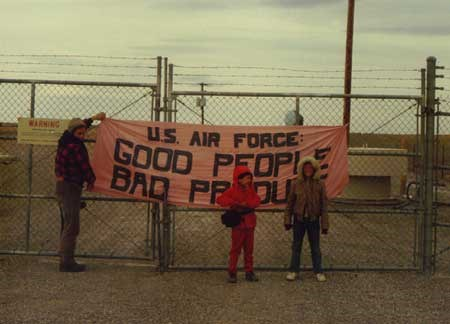 A group of people stand at a banner on a fence