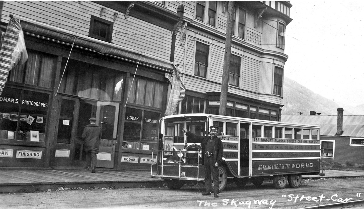 Man in uniform in front of streetcar.  He is pointing.  A large building is in background.