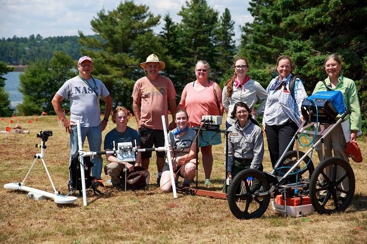 Men and women volunteers and park staff pose with archaeological equipment, outdoors.