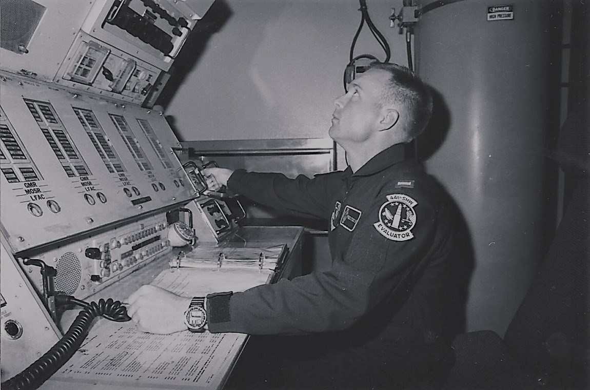 An officer seated in front of a tall electronic control panel.