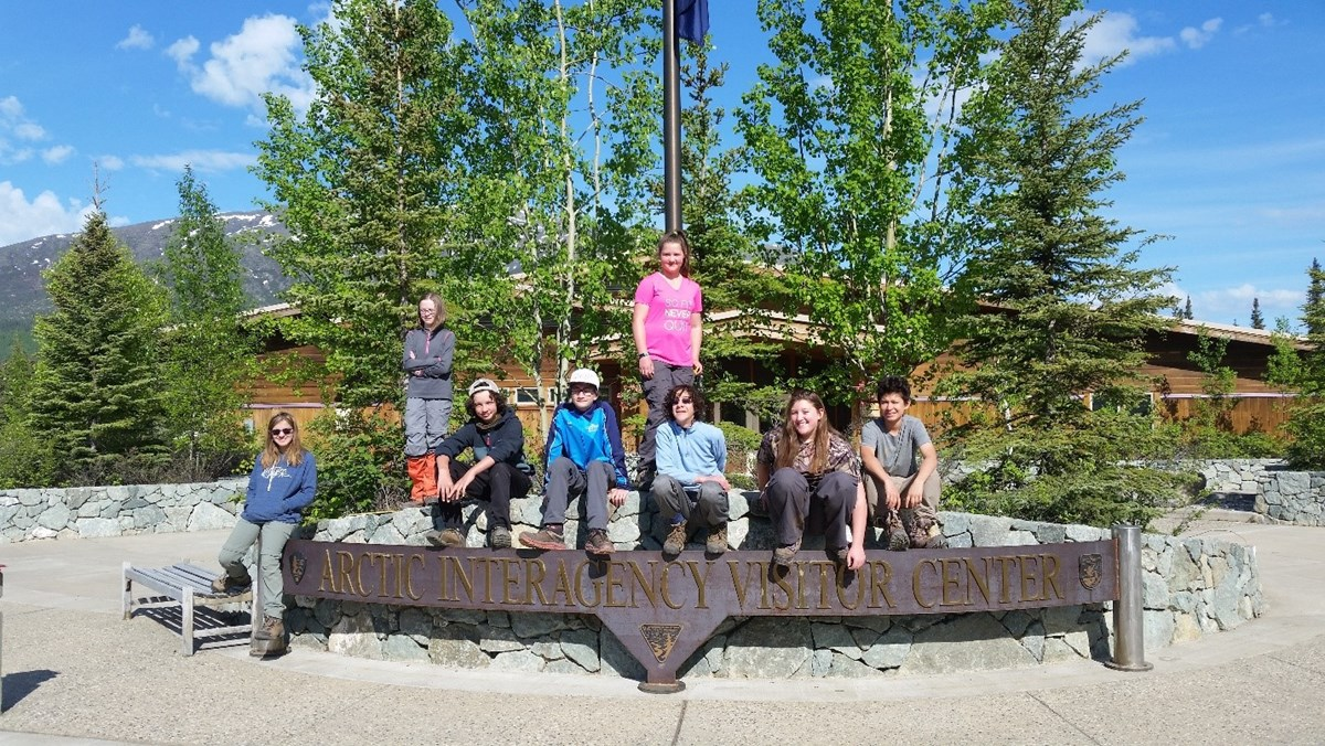 A group of eight students sit atop the Arctic Interagency Visitor welcome sign on a sunny day.