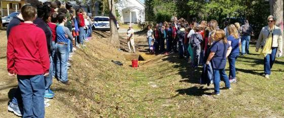 Students flank either side of a ditch dug by enslaved African Americans to enclose the prison camp.