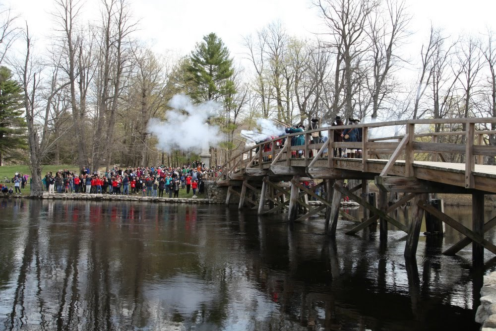 A wooden bridge stretches across the water while reenactors fire guns.