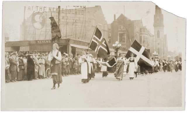 Women in Scandinavian dress holding flags marching down street with crowds on sidewalk