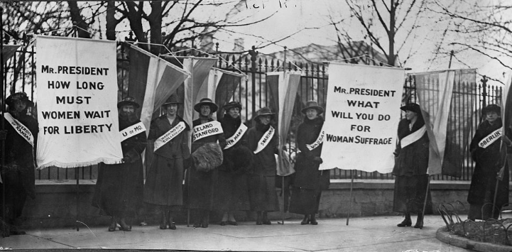 Women holding placards for women's suffrage in front of White House