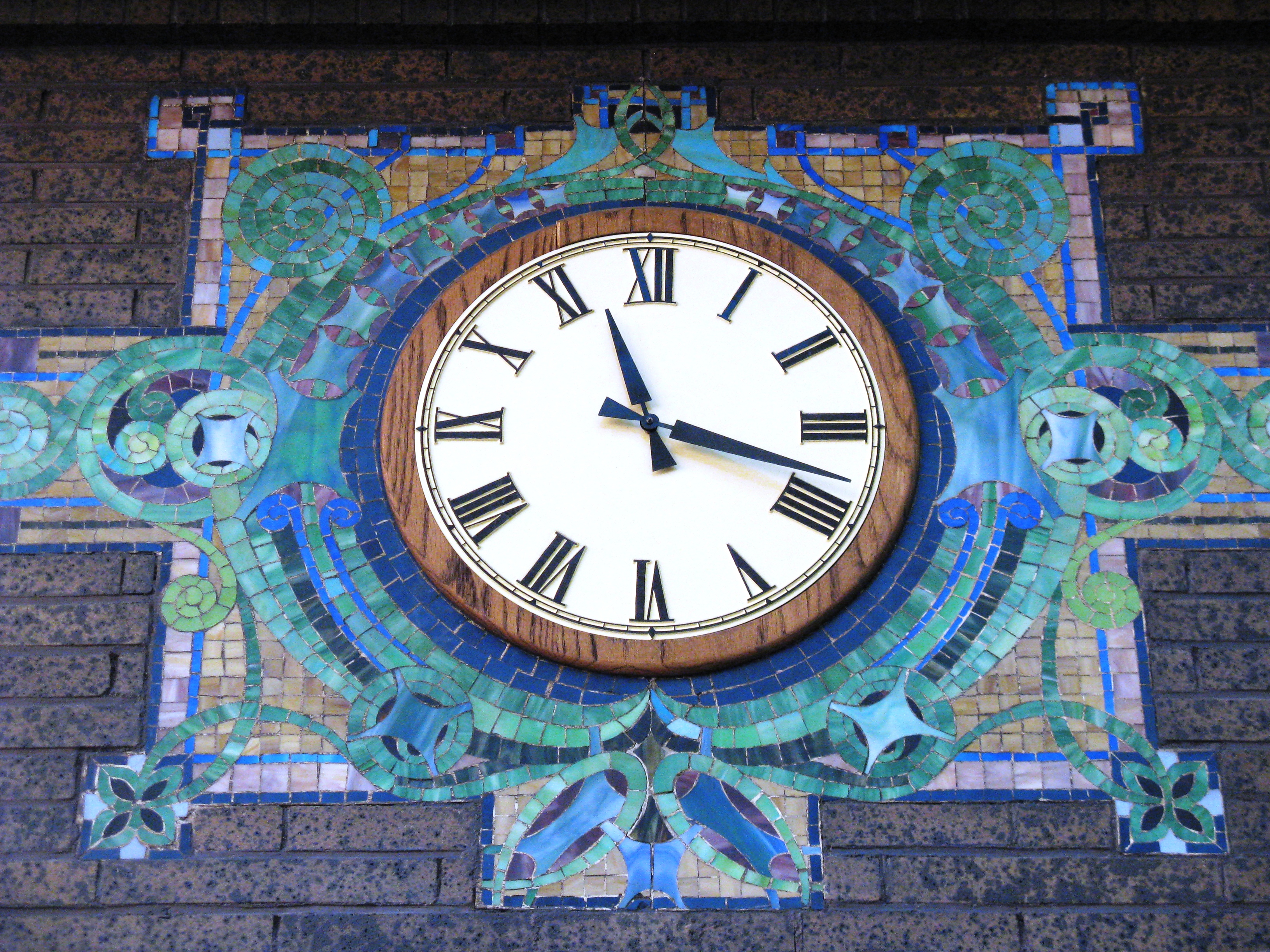 Clock with a colorful mosaic around it.