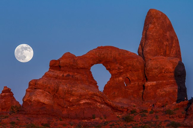 An arch formation at Arches National Park glows under the light of the full moon.