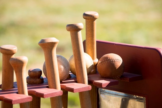 Close up of 1860s-style base ball bats and balls
