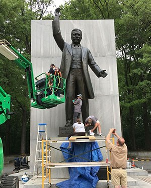 Cultural resource staff on foot and in a bucket lift clean the Theodore Roosevelt memorial statue.