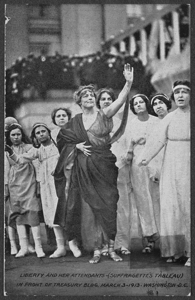 Photograph of women and girls in Greek costume in suffrage tableau in front of the Treasury Building, Washington, D.C. Central figure is dressed in toga as Liberty.