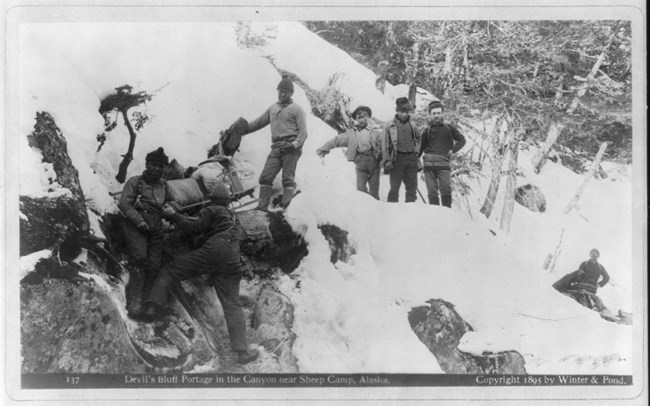 Men trying to haul a sled up a snow covered canyon