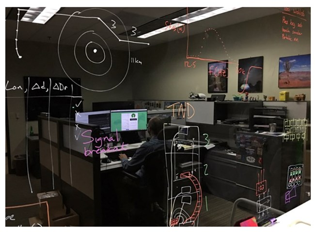 Damon Joyce's reflection is visible on the tech lab blackboard, where ideas develop and evolve.