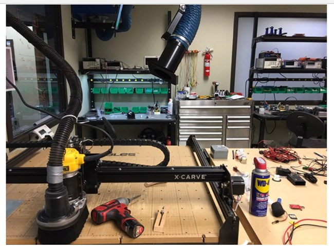 Tech shop view of metal cutting machine, power drill, WD-40 and other tools.