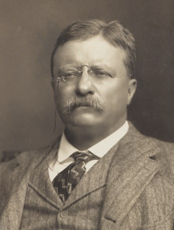 Theodore Roosevelt wears a suit and pince-nez