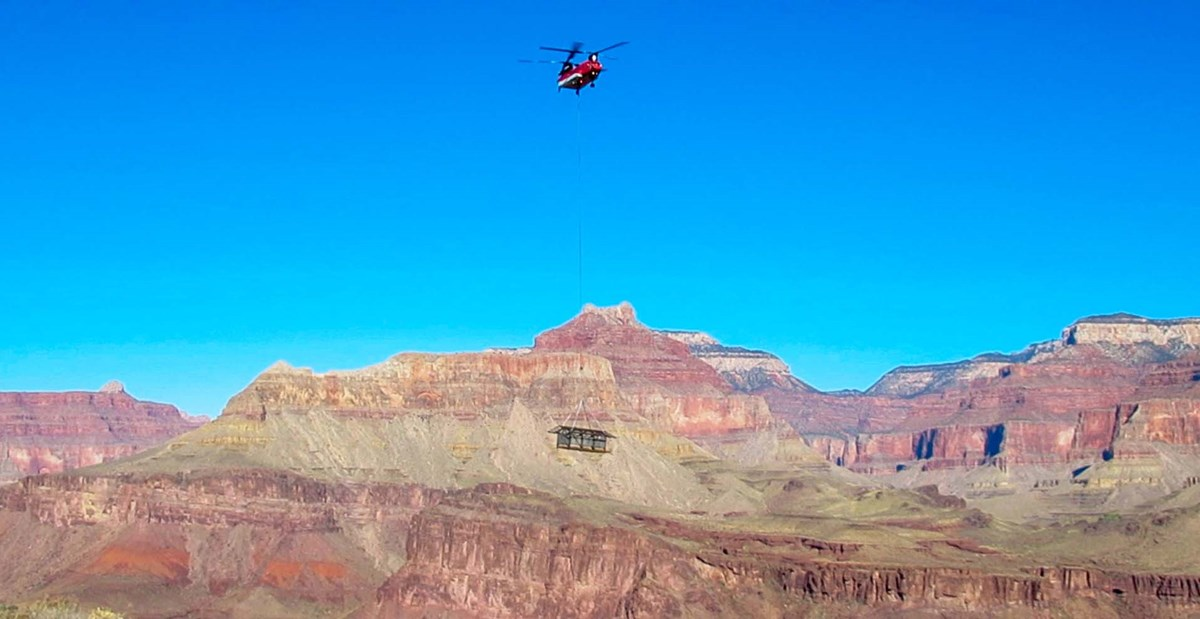 the framework of a 12 x 24 foot shade structure being lowered from a cable by helicopter, with colorful cliffs and peaks in the background.