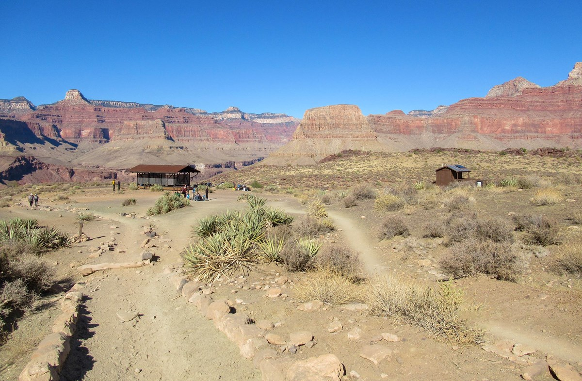 unpaved trails leading to two small buildings in a desert with colorful cliffs in the distance