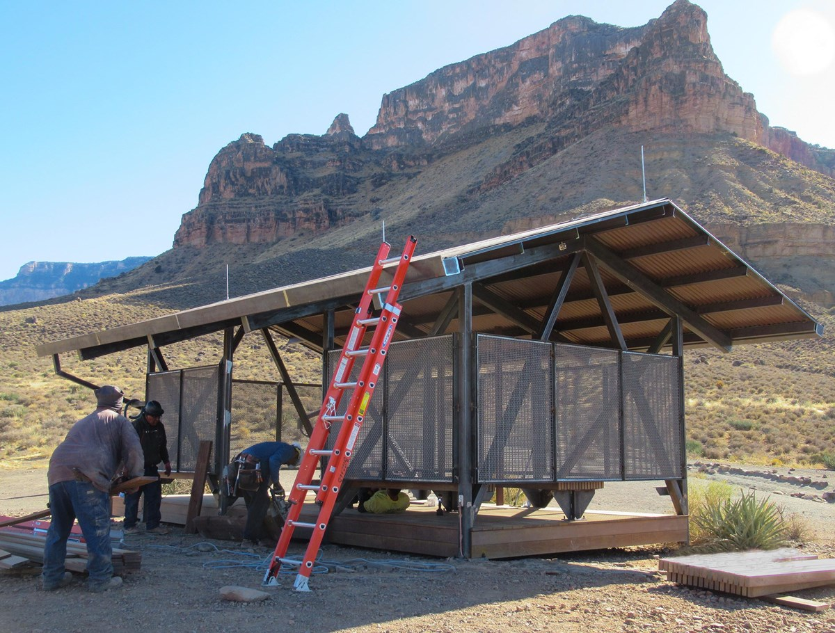 workers completing a 12 x 24 foot shade structure, in a desert, with a canyon wall rising in the distance