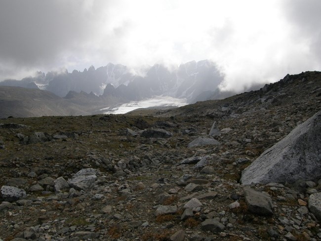 Image of rocky slope with high peaks and snow in background.