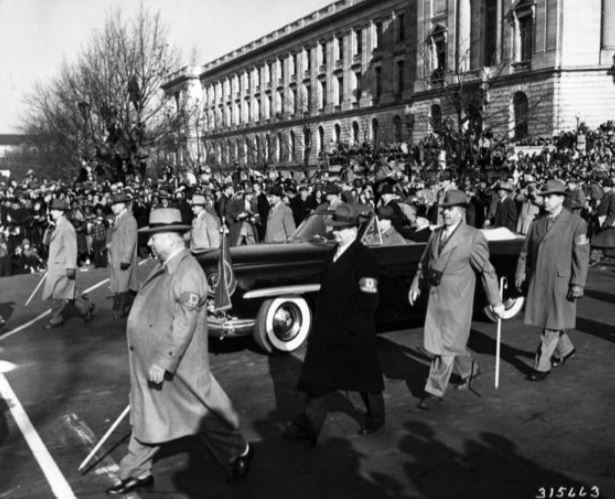 Harry Truman rides in a convertible car on Pennsylvania Avenue, flanked by men in trench coats