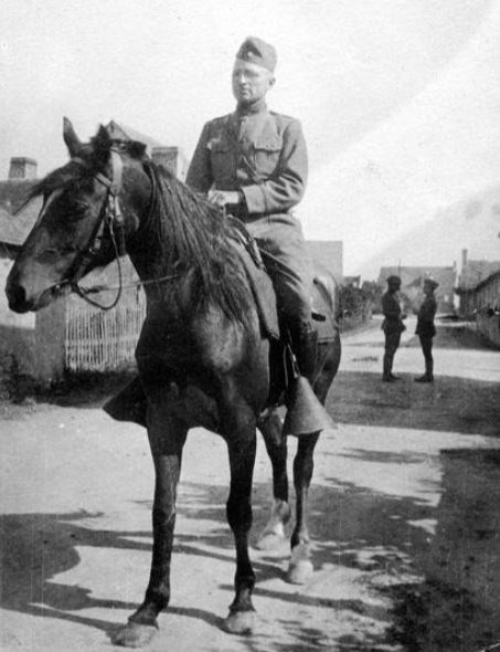Harry Truman, in military uniform, rides a horse on a village street.