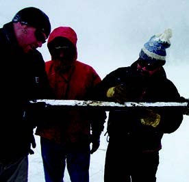 Three UNC researchers examine an extracted core from Bear Lake.