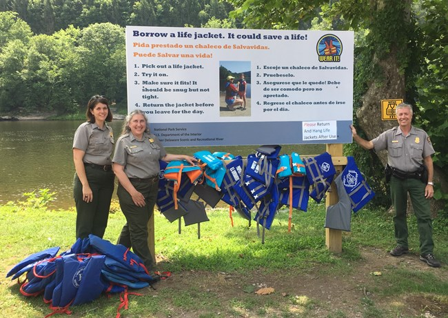 Park Rangers standing next to life jacket loaner station