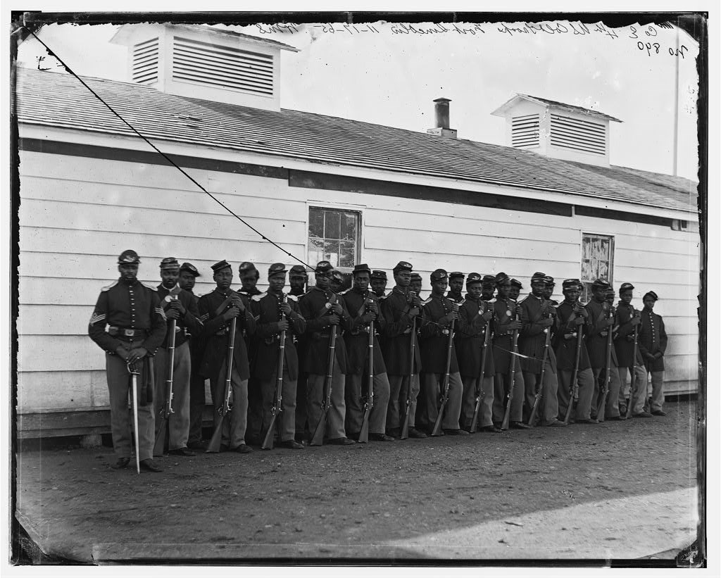 US Colored Troops stand in uniform in front of white building, B&W photo