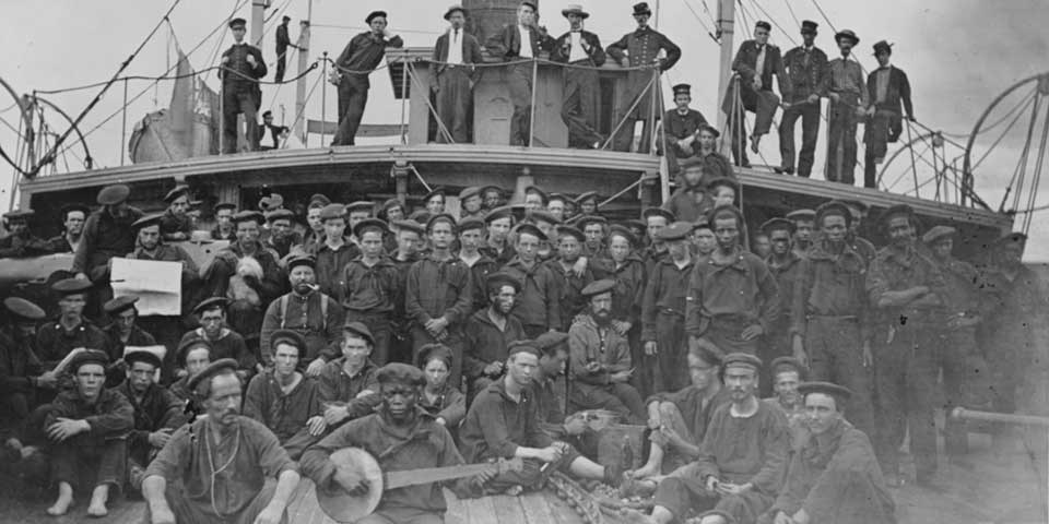 Black and white photograph of the crew aboard USS Hunchback. Some officers stand on a poop deck while most stand or sit on the main deck.