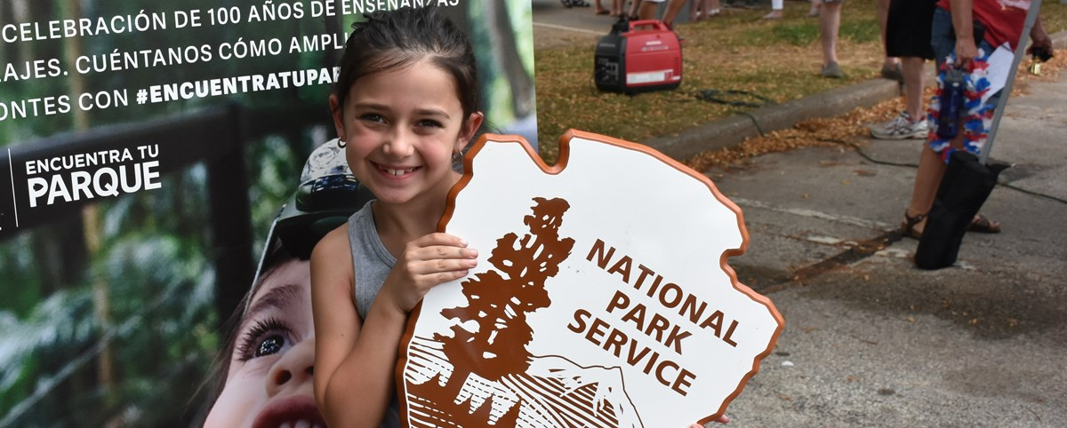 Child holding up a wooden NPS arrowhead logo