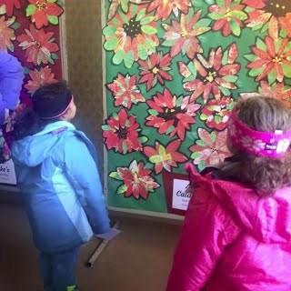 Children look at collages of poinsettia flowers