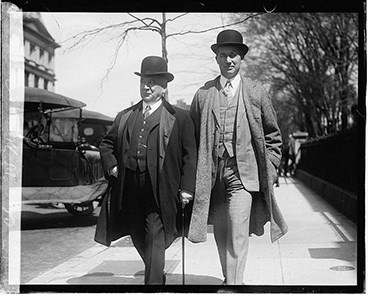 Charles W. and Benjamin W. Morse stroll down the street in three-piece suits and bowler hats.