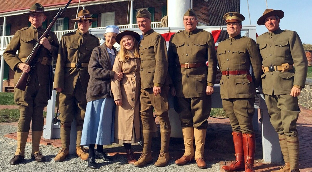 Visitors and staff are dressed in WWI uniforms and period costumes, while posing for a photograph.